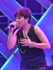 Chauhan singing a song, wearing a black top