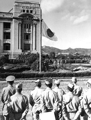 National Liberation Day of Korea - A Japanese flag at Seoul being lowered in 1945 as American soldiers watch.
