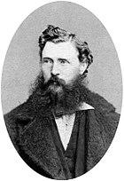 A dark-haired man with a scruffy beard