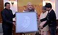 The Prime Minister, Shri Narendra Modi being presented a unique portrait made through IKAT weaving, created by Shri Surendra Meher, in New Delhi on December 10, 2014.jpg