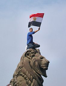 Man crouched on top of a large stone lion, waving a red, white and blue flag