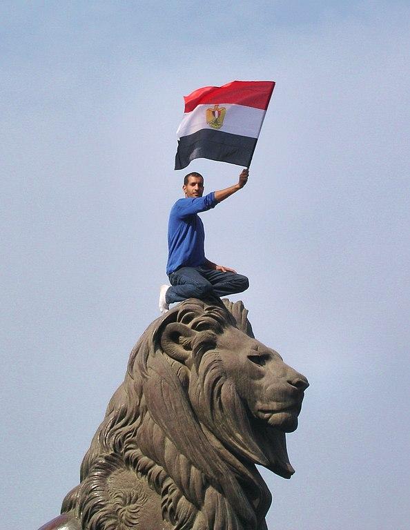 Seorang demonstran mengibarkanbendera Mesirdi atas patung singa di Jembatan Qasr an-Nil pada masaRevolusi Mesir 2011.