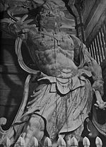 Ungyō. Front view of a scary statue with the right arm raised and carrying a weapon in his lowered left arm. Sculpted breastplate and necklace are visible.