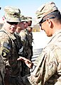 U.S. Army Brig. Gen. Clarence K. Chinn, right, the deputy commanding general for Afghan Development South, 101st Airborne Division (Air Assault), Combined Joint Task Force 101, gives Spc. Thaddeus Ivory 130606-Z-HL120-069.jpg