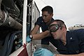 U.S. Navy Aviation Support Equipment Technician 2nd Class Miguel Carrillo, left, and Aviation Support Equipment Technician 3rd Class Justin West replace an oil can on a P25 fire truck aboard the aircraft carrier 130520-N-IG780-033.jpg