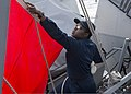 U.S. Navy Quartermaster 2nd Class Deneshea Gooden lowers a flag on the guided missile destroyer USS Stout (DDG 55) after refueling the ship during a replenishment at sea in the Mediterranean Sea Oct. 2, 2013 131002-N-UD469-483.jpg