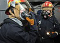 U.S. Navy fire party investigators breathe through their masks before investigating a mock fire-damaged area during a general quarters drill aboard the aircraft carrier USS Enterprise (CVN 65) while the ship is 110510-N-ZV753-011.jpg