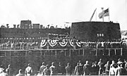 A large number of people are gathered around a platform erected just in front of a submarine.