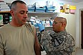 US Army 52428 BAGHDAD - Spc. Armando Reyes (left), a health care specialist from San Antonio, gives a flu shot to Staff Sgt. John Buchanan, of Phoenix City, Ala., at the Battalion Aid Station, on Camp Liberty, Oc.jpg