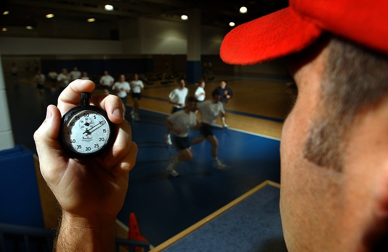 File:US Navy 030506-N-5862D-128 An instructor in the Freedom Hall athletic complex uses a stopwatch while recruits run a 1.5-mile track during a Physical Fitness Test (PFT).jpg