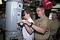 US Navy 040526-N-1876S-002 Master Chief Electronics Technician John C. Ketcham, Command Master Chief, Submarine Squadron Two, helps out Tyler Almquist as he peers through a periscope aboard USS Albuquerque (SSN 706).jpg