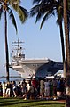 US Navy 050122-N-9076B-054 Arizona Memorial visitors watch as the Nimitz-class aircraft carrier USS Ronald Reagan (CVN 76), with Sailors manning the rails, is moored in Pearl Harbor, Hawaii.jpg