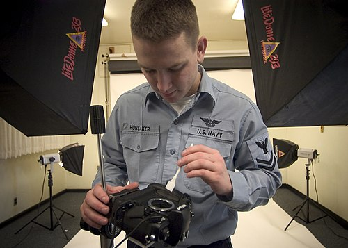 US Navy 050217-N-5134J-002 Photographer's Mate 2nd Class Lewis Hunsaker of Brownsville, Ore., uses a brush to clean a studio camera in the photo lab on board Naval Station Everett, Wash.jpg