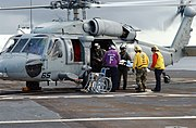 US Navy 050426-N-7027P-029 Personnel place a discharged Indonesian patient into an MH-60S Seahawk for transportation back to a hospital in Nias, Indonesia.jpg
