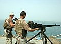 US Navy 050613-N-1825E-016 An Iraqi Sailor armed with a .50 caliber machine gun, foreground, stands duty with U.S. Navy Petty Officer.jpg