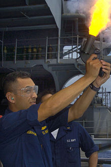 US Navy 050826-N-8604L-004 Lt. j.g. Armando Marron, fires a flare gun off the fantail aboard the conventionally-powered aircraft carrier USS Kitty Hawk (CV 63) during a routine training exercise.jpg