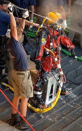 Professional diving - US Navy Diver being decontaminated after a dive. If the contamination was serious, the decontamination team would have been wearing hazmat gear