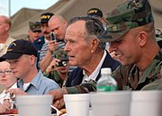 US Navy 051008-N-9274T-001 After arriving on board Naval Air Station Joint Reserve Base (NAS JRB), New Orleans, former President George H. Bush sits down to eat with military personnel