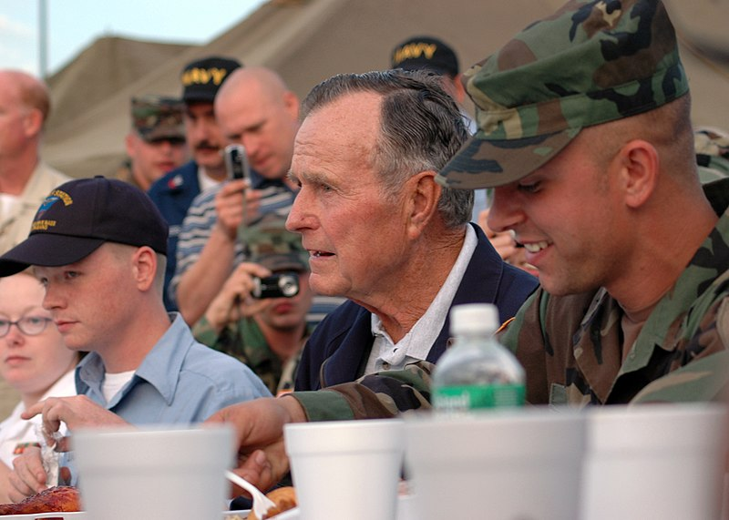 US Navy 051008-N-9274T-001 After arriving on board Naval Air Station Joint Reserve Base (NAS JRB), New Orleans, former President George H. Bush sits down to eat with military personnel.jpg