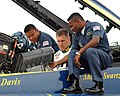 US Navy 060227-N-0050T-063 Aviation Machinist's Mate 1st Class Patrick Palma, left, and U.S. Marine Sgt. Deo Harrypersaud, right, prepare Busch Series NASCAR driver Mark McFarland, prior to a VIP demonstration flight.jpg