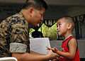 US Navy 070821-N-1467K-106 Capt. Yves Nepomuceno, embarked aboard amphibious assault ship USS Peleliu (LHA 5), asks an Micronesian boy where he hurts during a medical civic action program at the Tafunsak government building in.jpg