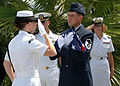 US Navy 080819-N-7974M-008 U.S. Air Force Master Sgt. Jeff Wheeler receives an American flag from a Navy honor guard detail during a scattering of ashes ceremony honoring his grandfather and Pearl Harbor survivor, Major Wheeler.jpg