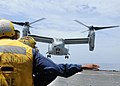 US Navy 100715-N-8069G-185 Boatswain's Mate 3rd Class Viviana Milos directs a Marine Corps V-22 Osprey onto the flight deck of the amphibious dock landing ship USS Carter Hall (LSD 50).jpg