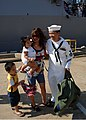 US Navy 110727-N-YF783-046 Electrician's Mate 1st Class Eugene Andal greets his wife and children during a homecoming celebration for USS Mason (DD.jpg