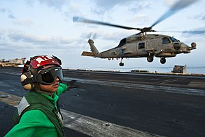 US Navy 120108-N-BT887-007 Airman Joyce Cruz checks for a clear deck before signaling to an MH-60R Seahawk from the Raptors of Helicopter Maritime.jpg