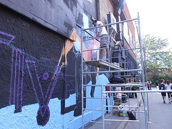 Young people standing on a ladder spray painting art on the side of a building.