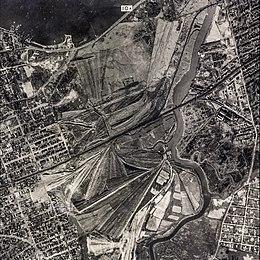 """George Wilson ja hänen vaimonsa Myrtle elävät """"tuhkanlaaksossa"""", joka on historiallisesti New Yorkissa 1920-luvulla sijaitsevassa jätteenkäsittelylaitoksessa (esitetty yllä olevassa valokuvassa).  Nykyään alue on Flushing Meadows – Corona Park."""