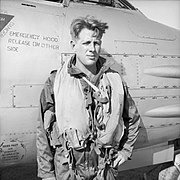Informal half portrait of blond man in flying gear in front of aircraft