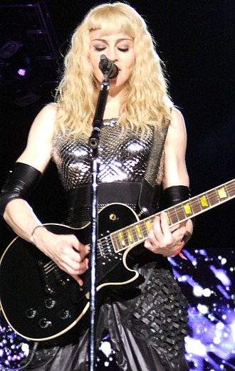 "Ray of Light (song) - Madonna, wearing a futuristic outfit and playing the electric guitar, singing ""Ray of Light"" during the 2008–2009 Sticky & Sweet Tour."