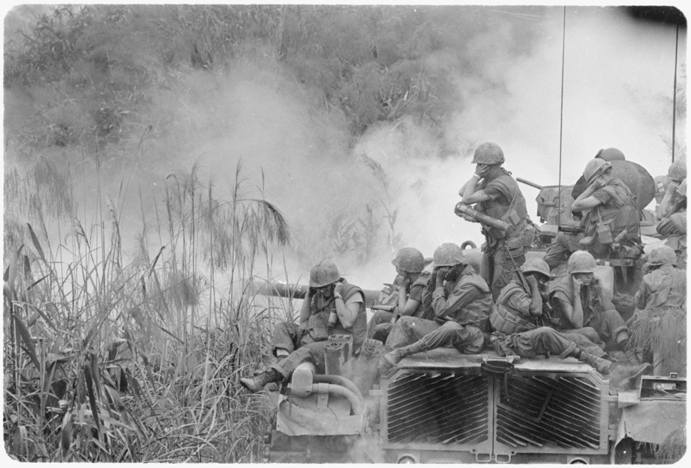 Vietnam....Marines riding atop an M-48 tank cover their ears as te 90mm gun fires during a road sweep southwest of... - NARA - 532483