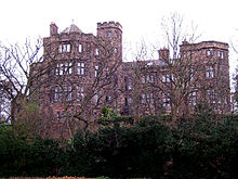 Seen from a low angle through the branches of trees is a substantial stone house with two-three storeys, bay windows and some castellation.