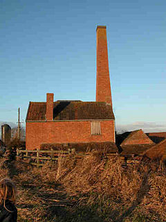 Red brick industrial building with tall chimney.