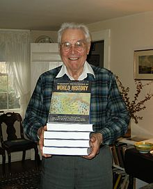 Smiling older man holding a stack of books in front of him; the top one is tilted up so the title, World History, is visible.