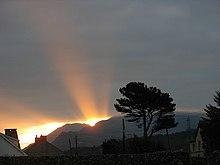 Sur un fond nuageux un rayon de Soleil perce au-dessus d'une montagne.