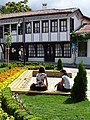 Women with Backdrop of Facade of Buhalov Han (Owl's Inn) - Karlovo - Bulgaria (41492106970).jpg