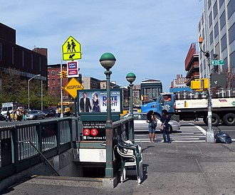135th Street (IRT Lenox Avenue Line) - Northbound staircase on the southeast corner. An elevator on the northeast corner can be seen in the background.