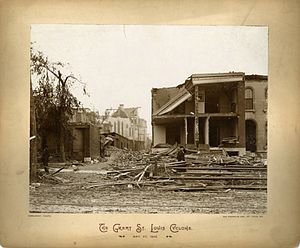 1896 St. Louis–East St. Louis tornado - Park Avenue residence with woman walking by. A 'for sale' sign can be seen lying next to almost completely demolished building. Row of shacks in front of church left untouched. The State Historical Society of Missouri.
