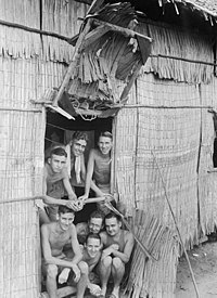 Shirtless and malnourished men smiling in a in the doorway of a hut