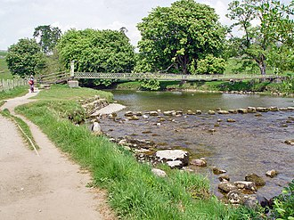 Hebden, North Yorkshire - The River Wharfe is crossed by a suspension footbridge and stepping stones