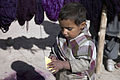 A young Afghan child tries to figure out how to remove the back of a sticker, given to him by members of the Female Engagement Team (FET), during a humanitarian mission in Kandahar province, Afghanistan, Jan. 6 120106-A-RX742-048.jpg