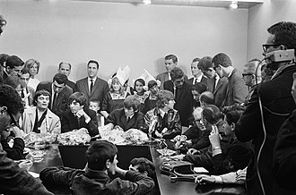 Cultural impact of the Beatles - Beatlemania: Fans and media swarm the Beatles at Schiphol Airport in Amsterdam, 1964