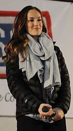 A brunette woman wearing a black jacket and gray scarf smiles