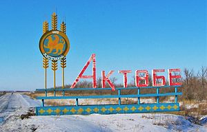 Aktobe - Aktobe coat of arms on road side sign at the city limit