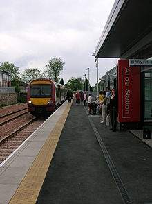A railway platform with a train stopped at the station. A few passengers are scattered along the platform