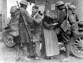 Two soldiers are warmly greeted by civilians - and elderly woman and man. A parked ambulance is behind them