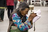 An elderly Tibetan women holding a prayer wheel on Lhasa, Barkhor.jpg